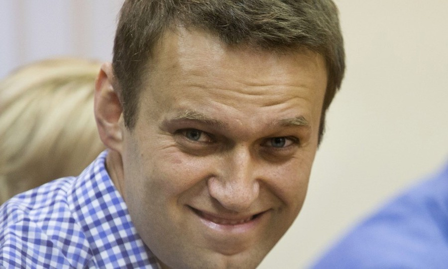 Russian opposition leader Alexei Navalny smiles as he listens to judge in a court in Kirov, Russia on Thursday, July 18, 2013. A Russian judge on Thursday found Navalny guilty of embezzlement, a finding that could bring the charismatic anti-corruption blogger and Moscow mayoral candidate up to six years in prison. (AP Photo/Evgeny Feldman)